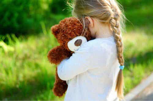 von einem Elternteil verlassen - Mädchen umarmt ihren Teddy