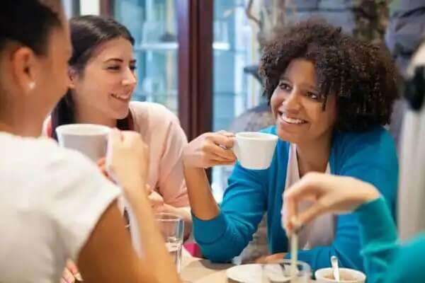 Eine Frauengruppe unterhält sich und trinkt dabei Kaffee, um neue Leute kennenzulernen